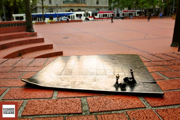 Bronze Chess Board - Resting on the Morrison Street fallen column, three bronze chess boards, designed by Soderstrom Architects P.C., showcase the chess playing activities that occur on the Square. Photo Credit: Robert Vest