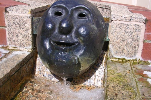 Five bronze cast masks, designed by Will Martin, reside in the water trough surrounding the back patio of Starbucks.